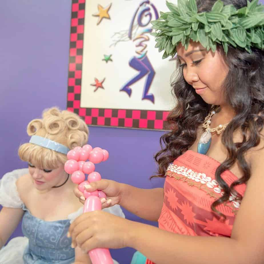 Two girls in fancy dress shaping balloons for a kids birthday party