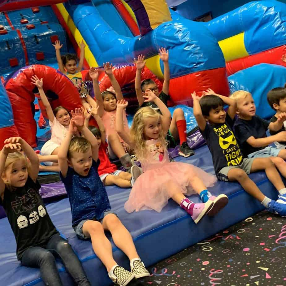 Bouncy indoor play ground full of smiling kids - great for kids birthday parties!
