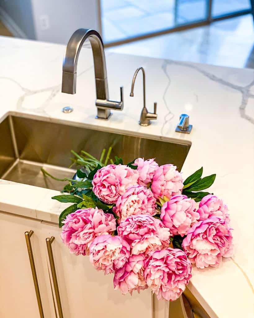 Freshly cut peonies in kitchen sink