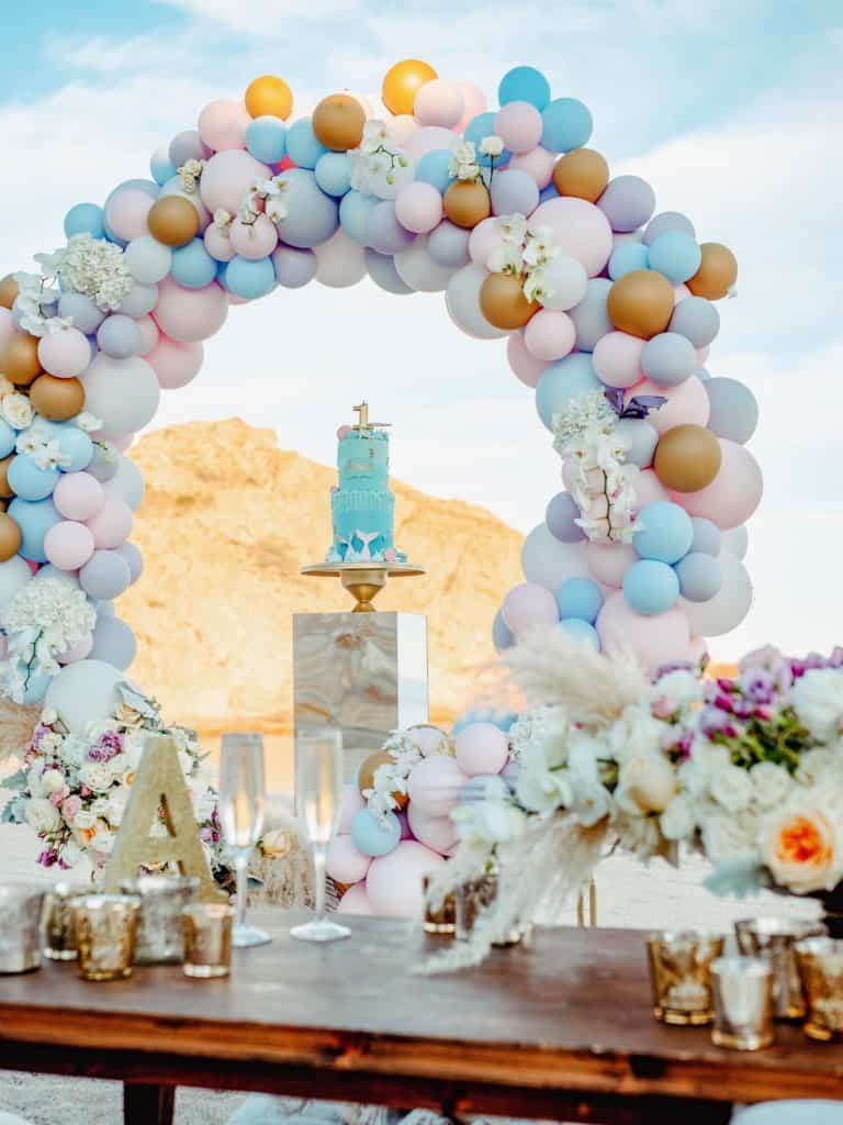 Balloons, blue cake, and party table on the beach
