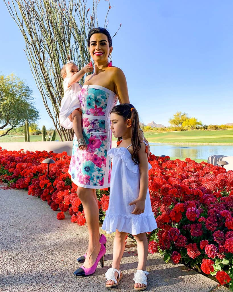 Mom and daughters on walk by flowers and lake. Ideas for Mother's Day activities and gifts