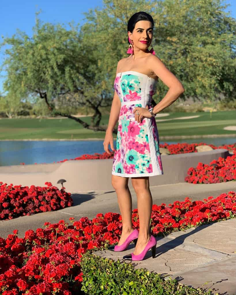 Tall brunette woman in floral dress by lake and flowers