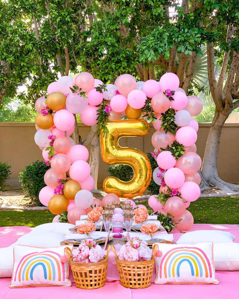 My 5 Year Old's Birthday Party at home with balloon arch, table settings and pink decorations