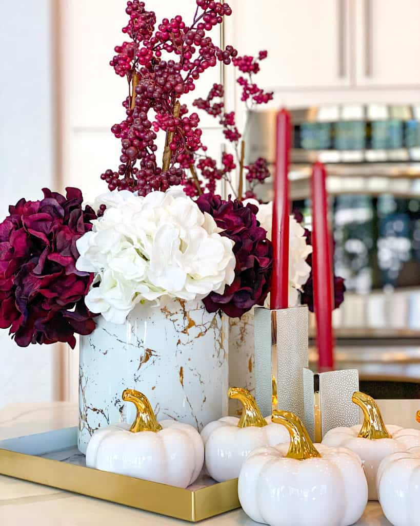 Fall themed decor display: white and burgundy faux flowers, candles and ceramic pumpkins