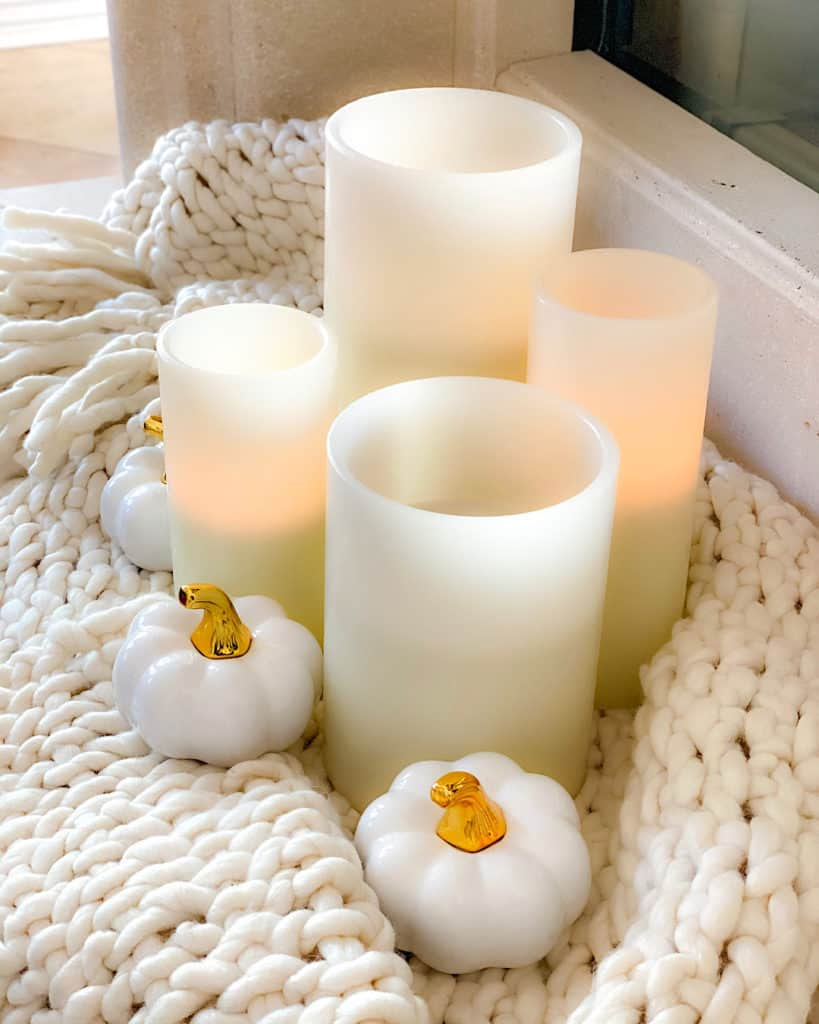 Stylish fall decor ideas for your living room: white throw set off with candles