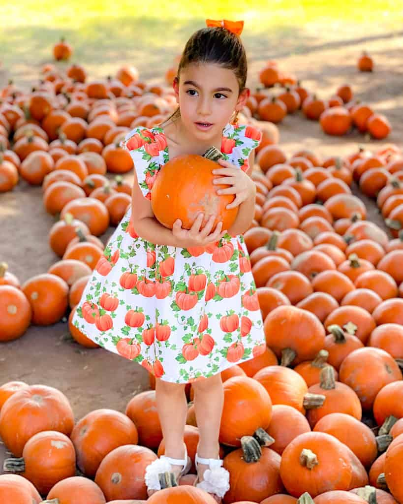 My eldest in a cute pumpkin dress at the pumpkin patch: top tip, take a change of clothes!