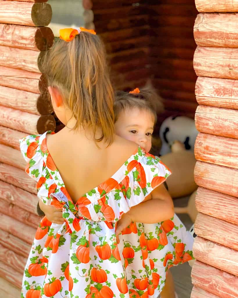 Sisters in matching dresses having a great day out at the pumpkin patch