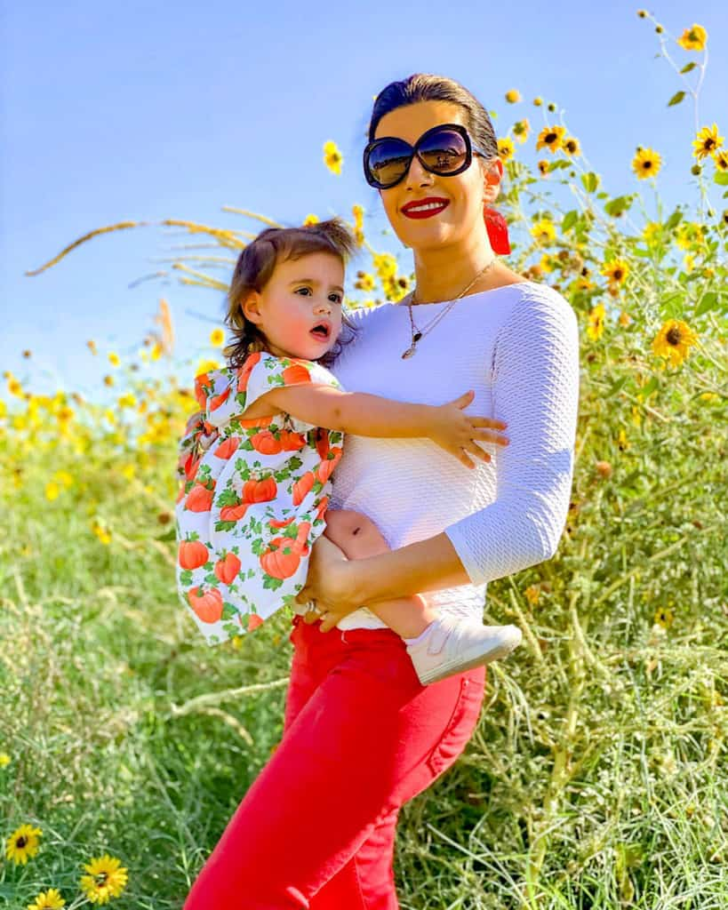 Taking your toddler to the pumpkin patch. Mom and daughter pose by sunflowers