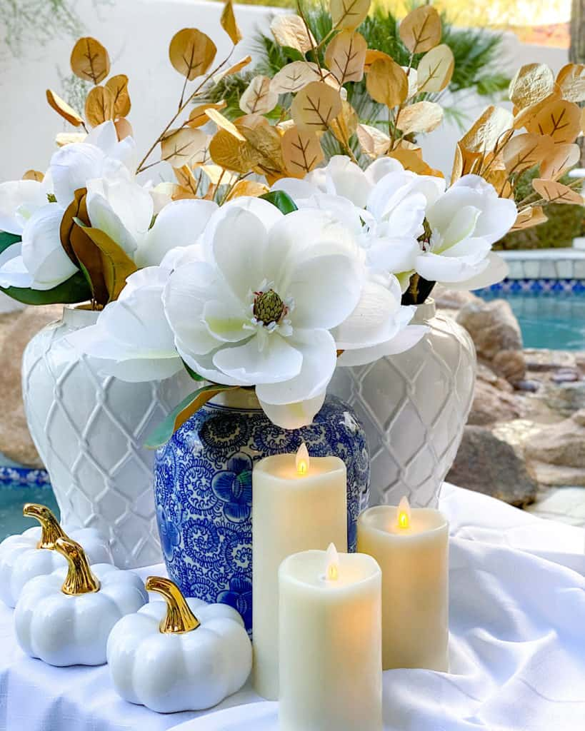 Blue and white vase, candles and pumpkins for Thanksgiving decorations