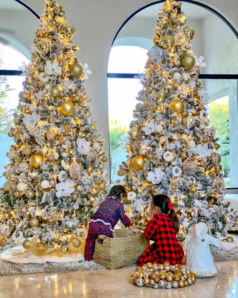Two girls decorating White and Gold Christmas trees