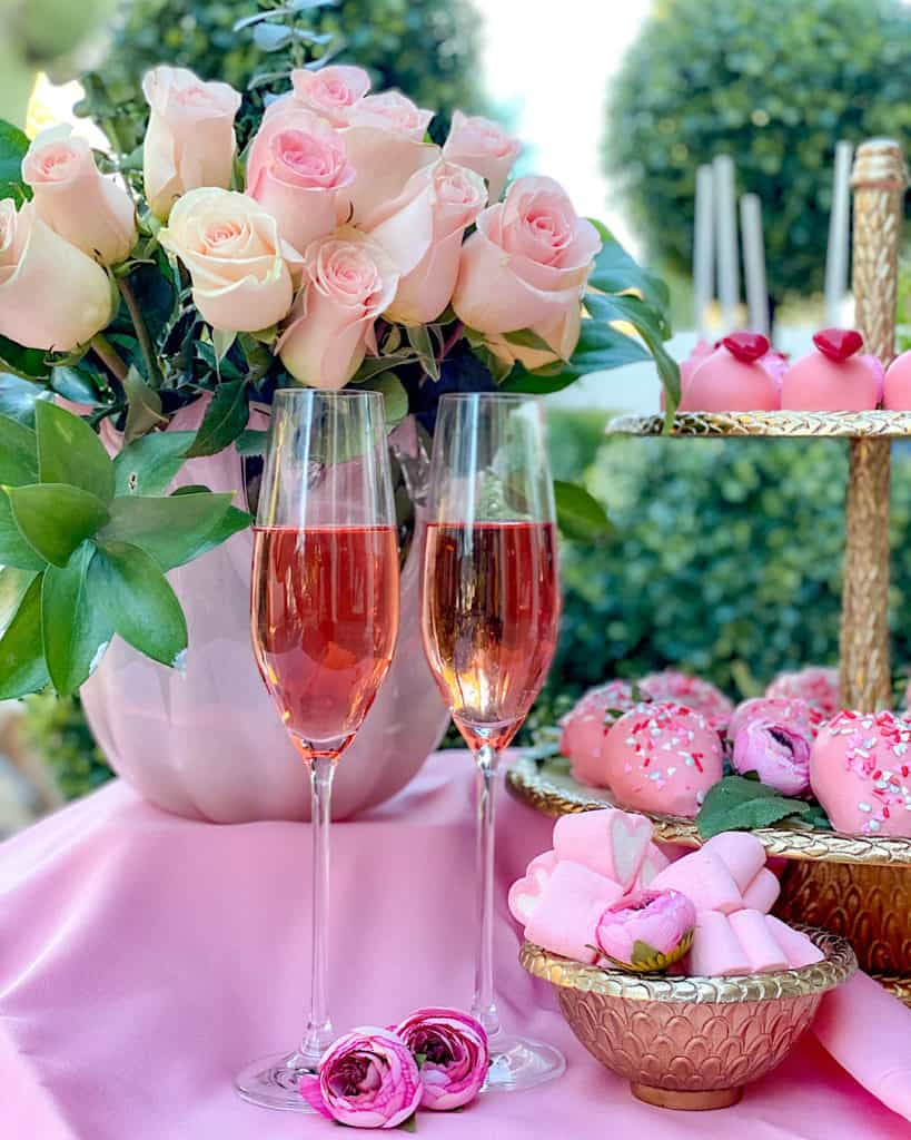 Pink roses, pink champagne and bowls of sweets on a Valentine's Day Dessert Table