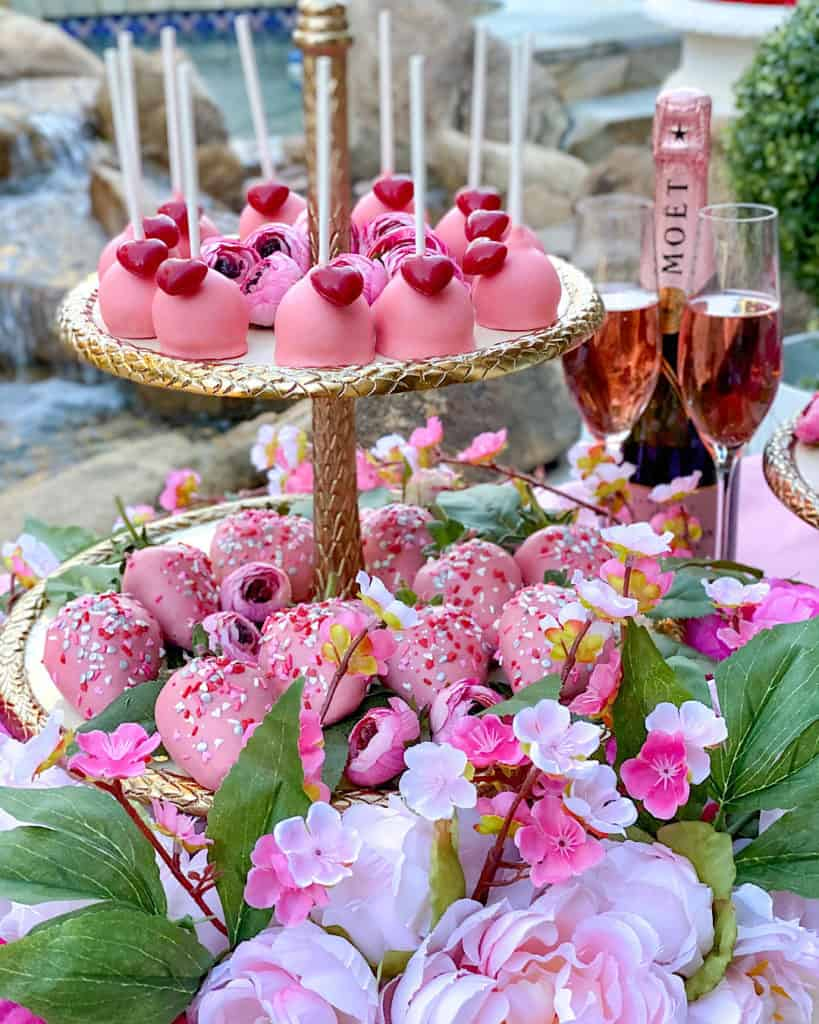 Pink cake pops and pink champagne glasses with Moet bottle on a Valentine's Day Dessert Table