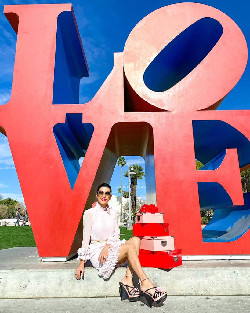 Valentine's Day Gift Ideas for Her - woman sitting underneath large LOVE sign, in pink dress with pink gift boxes.