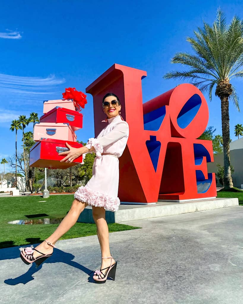 Woman in pink dress with gift boxes, LOVE sign in background. Valentine's day Gift Ideas.