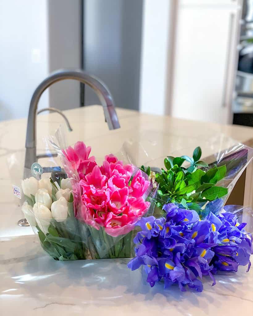 Freshly cut flowers by kitchen sink