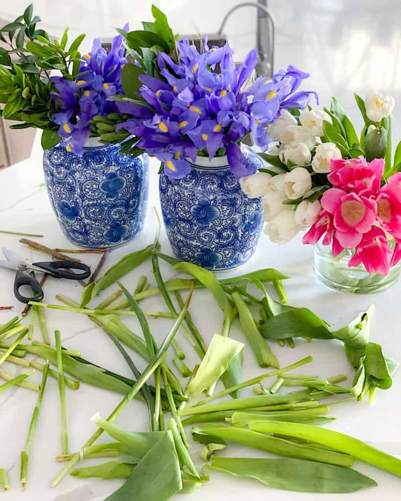 Irises in blue vase, tulips in clear vase.