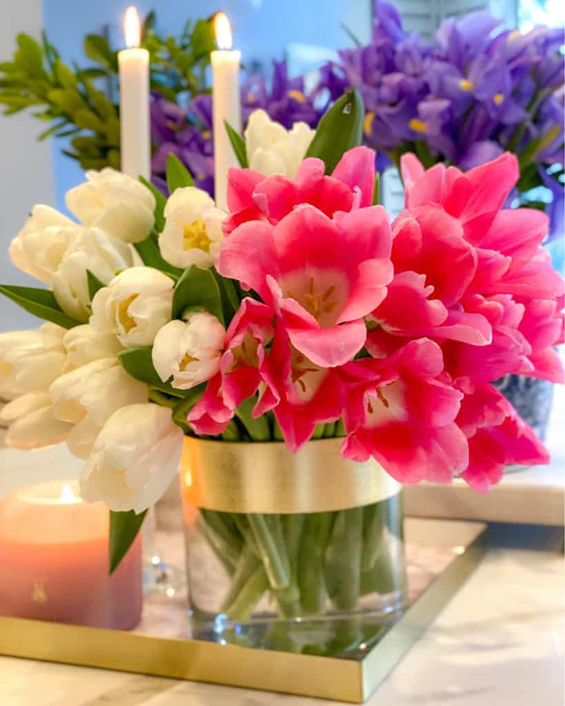 Candles and tulips in a vase.