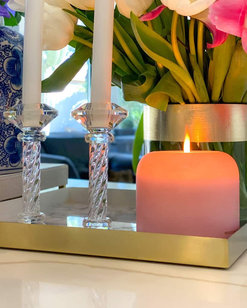 Pink candle and crystal candlesticks on a tray.