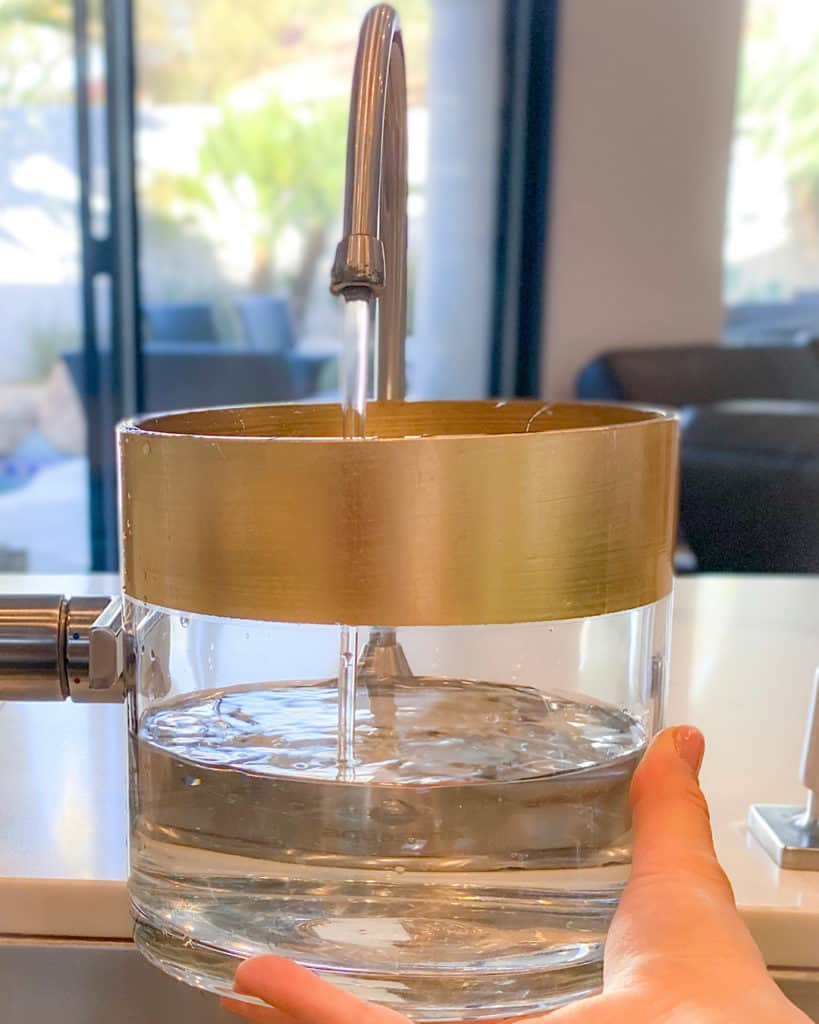 Filling glass vase with water