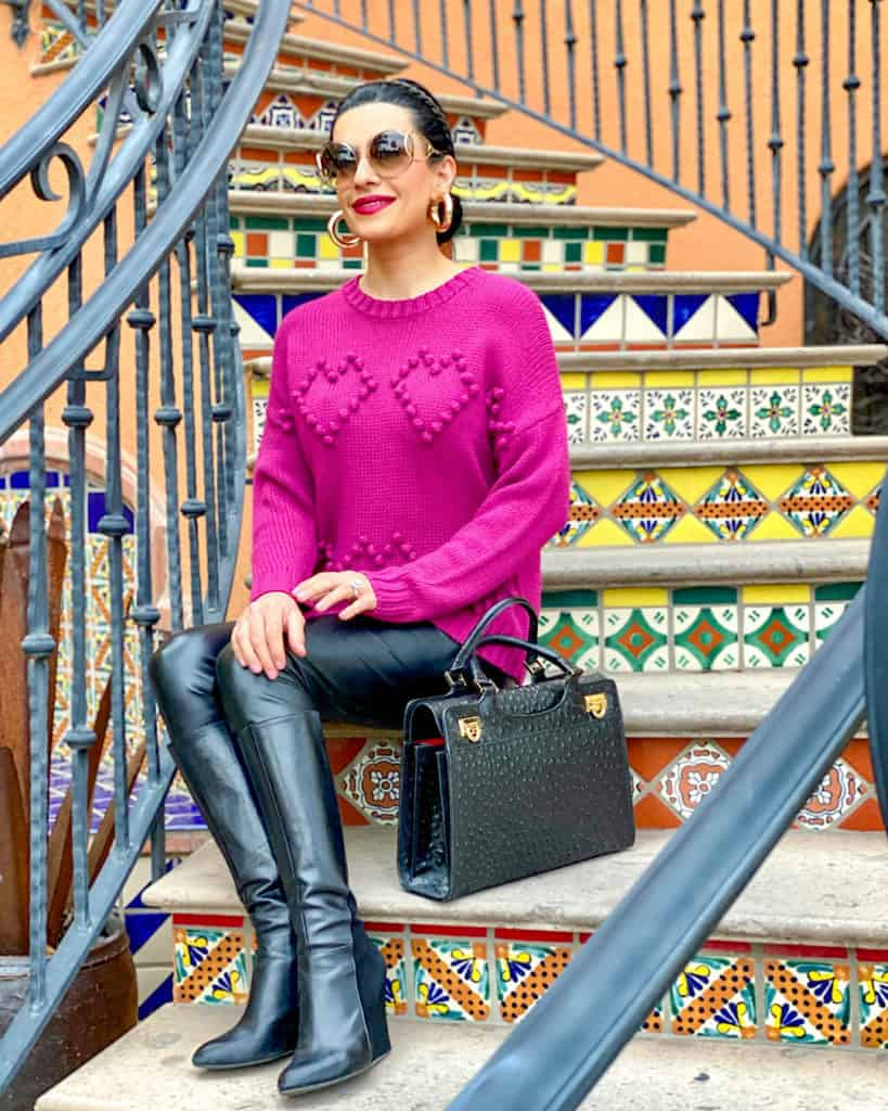 Ideas on what to wear on Valentine's Day - woman sitting on steps wearing pink lipstick, pink sweater with black bag and boots.