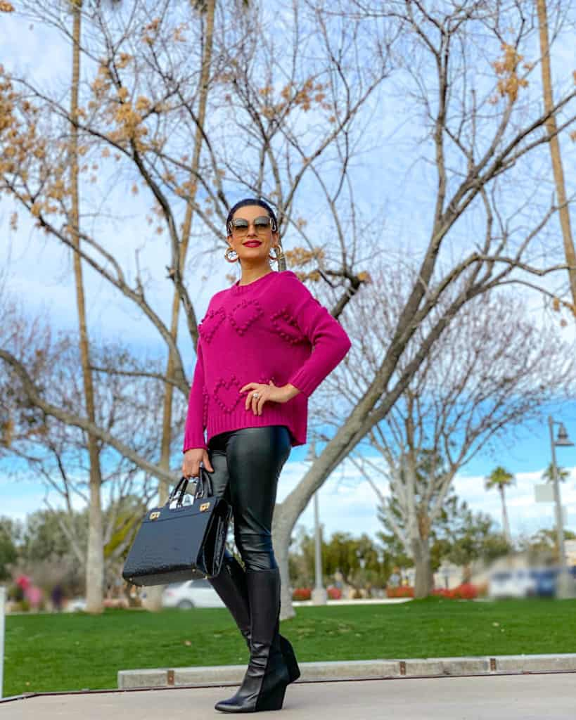 A lady standing with heart shapes sweater- What to wear on Valentine's Day guide!