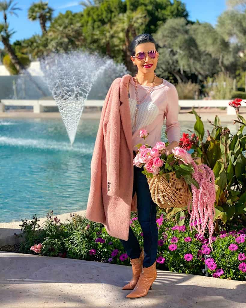 A woman wearing a pink coat, holding pink flowers in a basket: What to wear on Valentine's Day tips