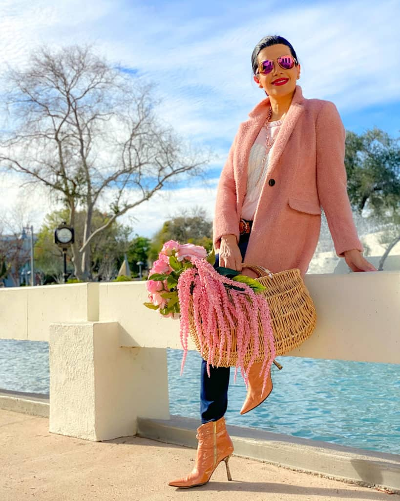 A woman wearing a pink coat holding pink flowers in a basket: inspiration for what to wear on Valentine's Day