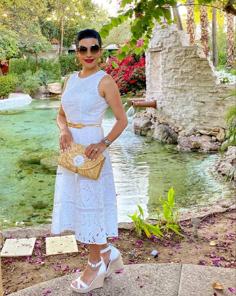 Woman wearing white dress, white wedge sandals and clutch bag