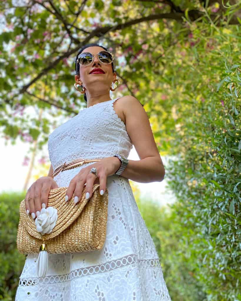 Woman wearing white dress and clutch bag
