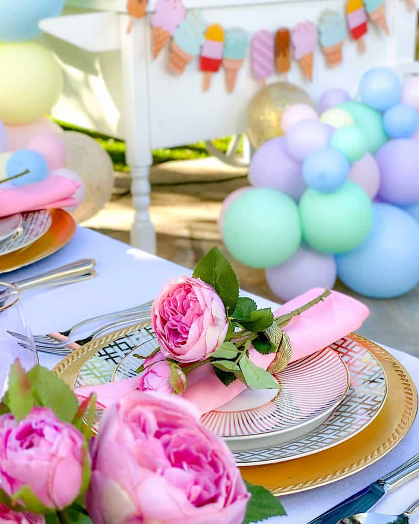 Table settings, flowers and balloons for ice cream birthday party.