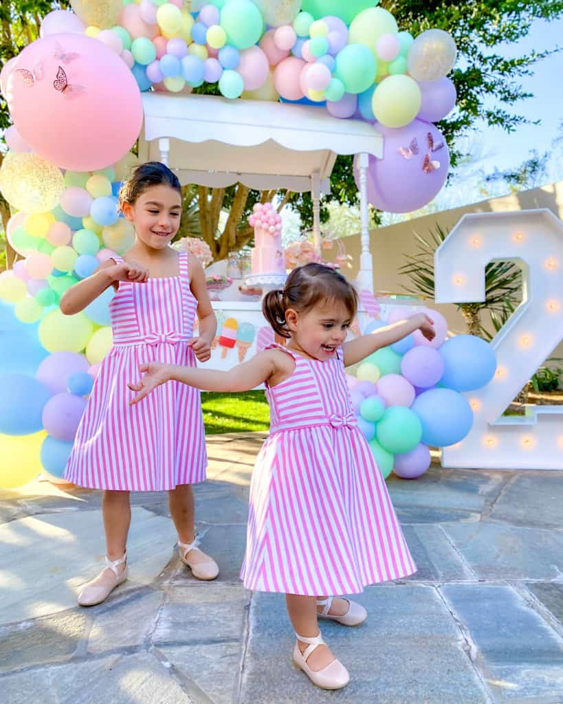 2 girls in striped dresses with balloons in background