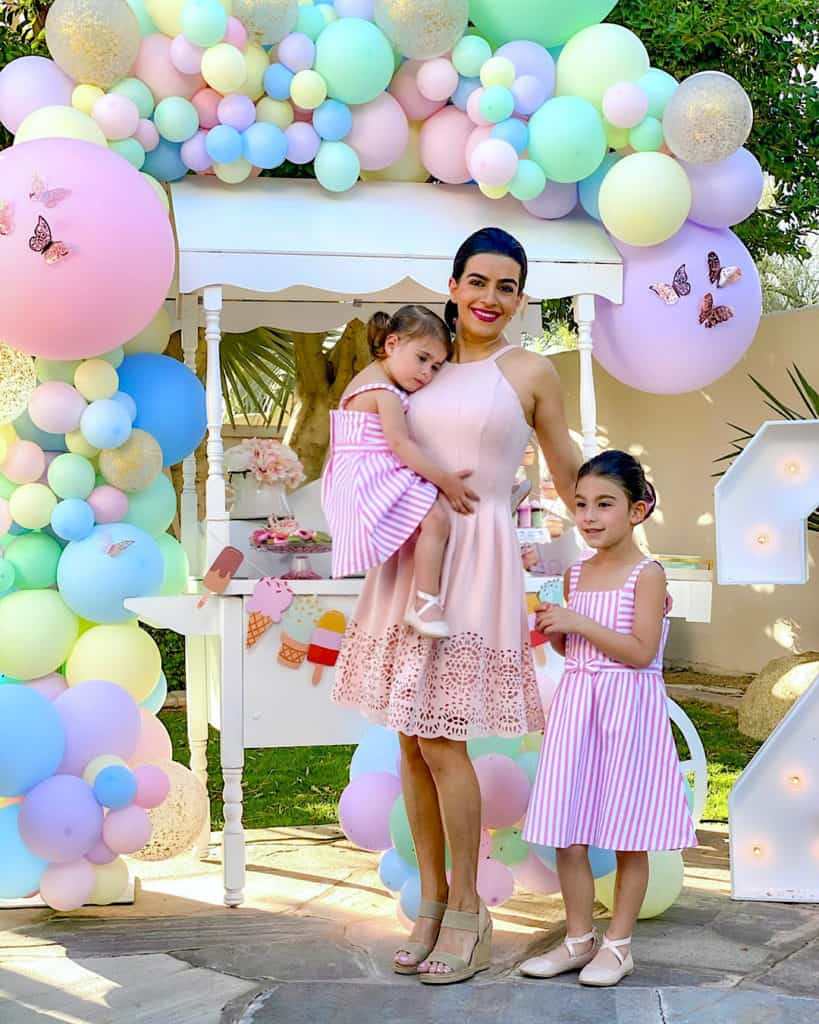 Mother and daughters beside ice cream cart and balloons.