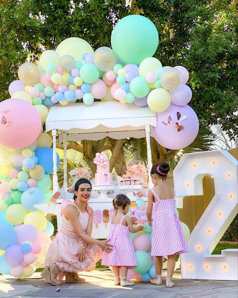 """Mother and daughters beside ice cream cart, balloons and large lit up """"2"""" sign."""