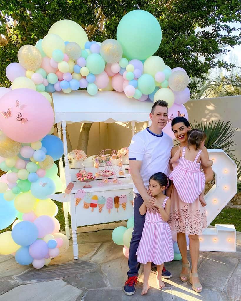 Family standing beside ice cream cart.