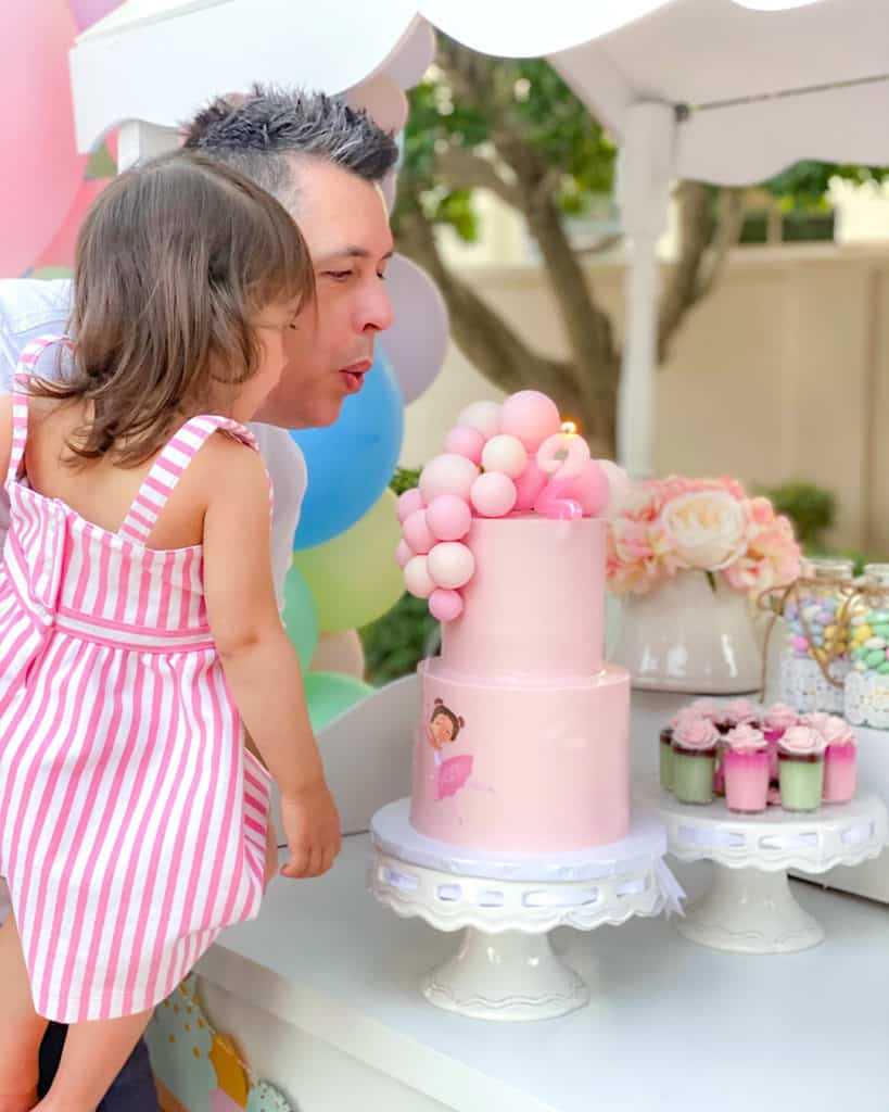 Girl and her dad blowing out birthday candle on Cinderella cake.
