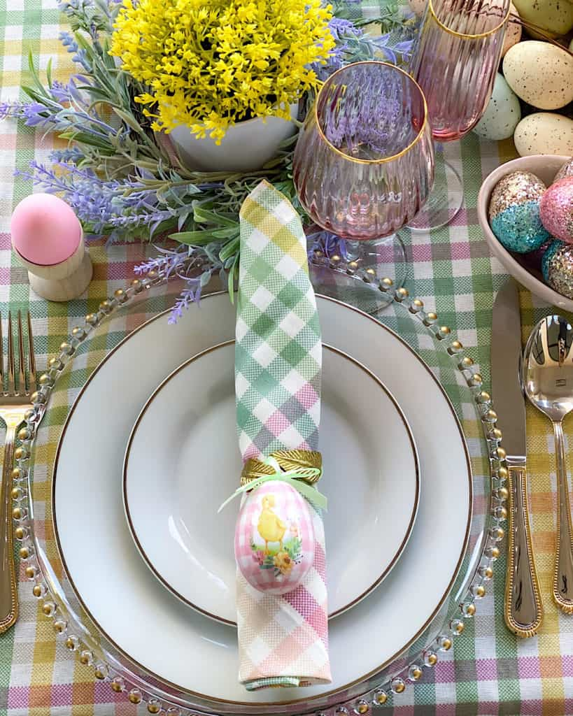Easter Sunday brunch table place setting with napkin, flowers and Easter decorations