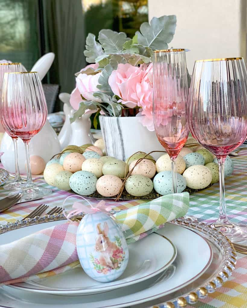 Easter treats and flowers on dining table with pink glassware.