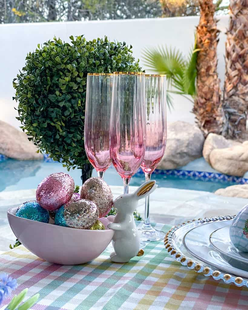 Pink champagne glasses and easter decorations on outdoor dining table