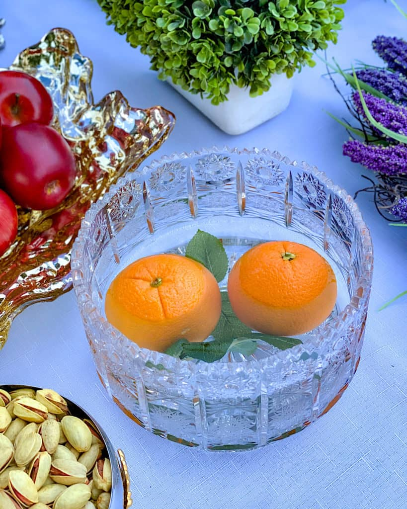 A crystal bowl of water with an orange: Nowruz table decorations