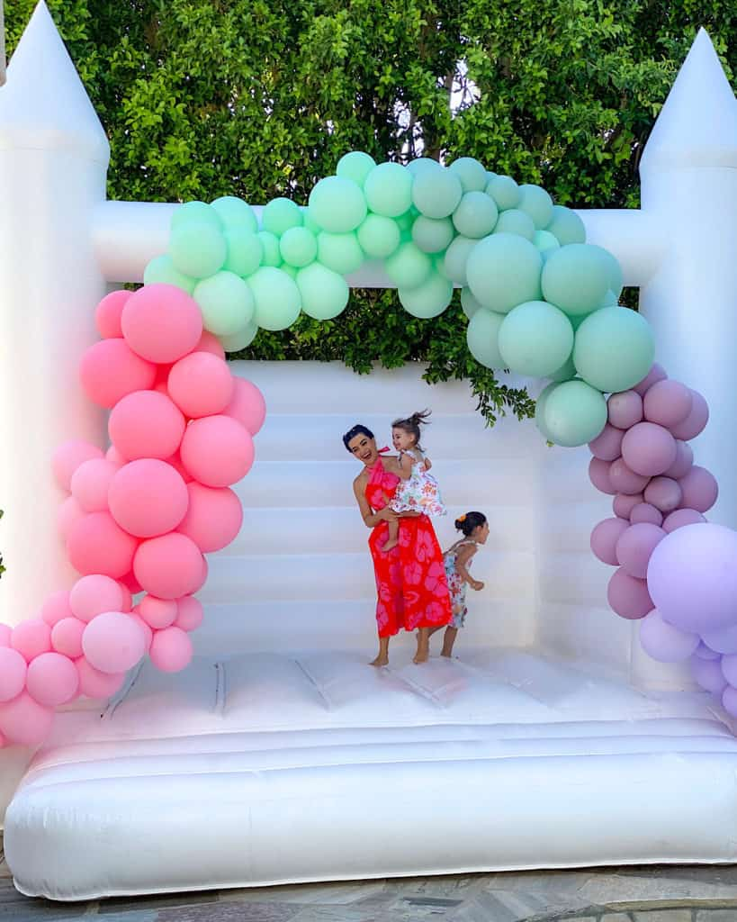 White Bounce Castle with balloons and mother and daughters