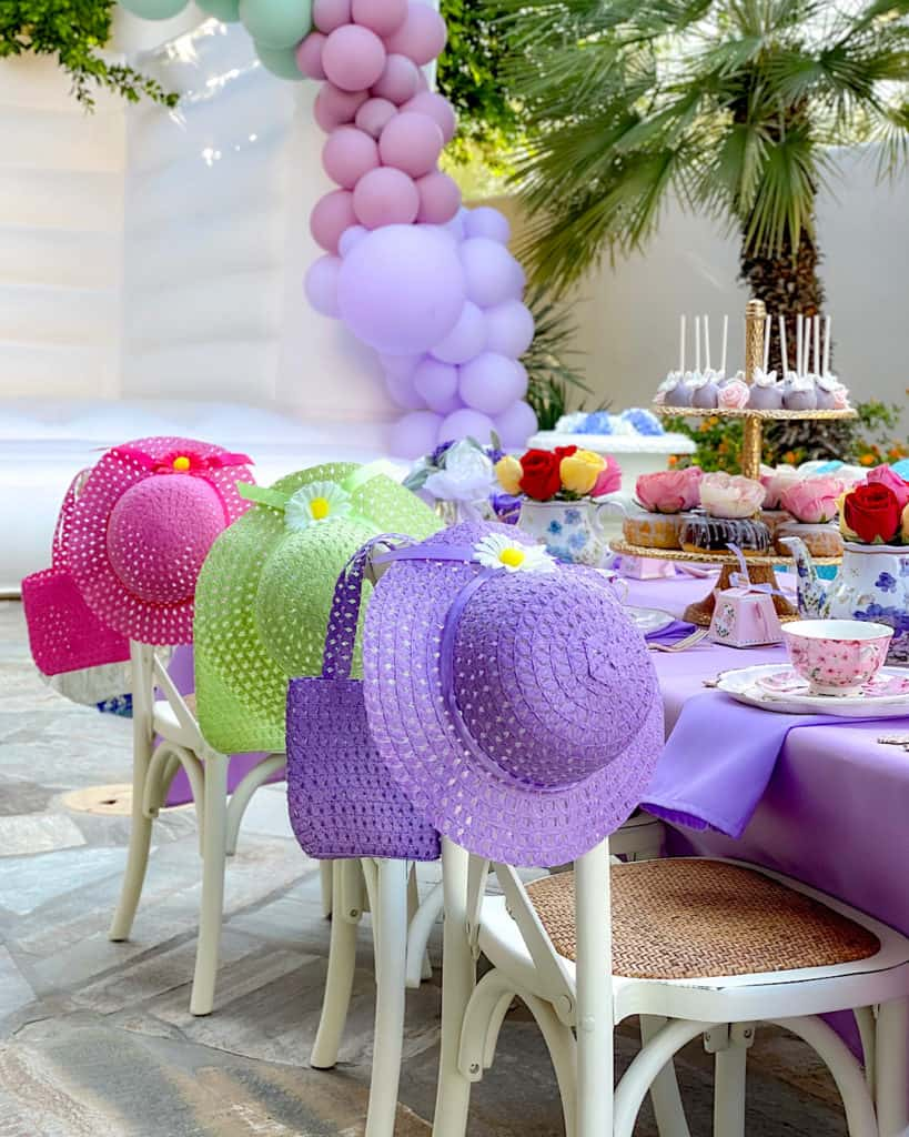 Purple, green and pink straw hats at an outdoor birthday party