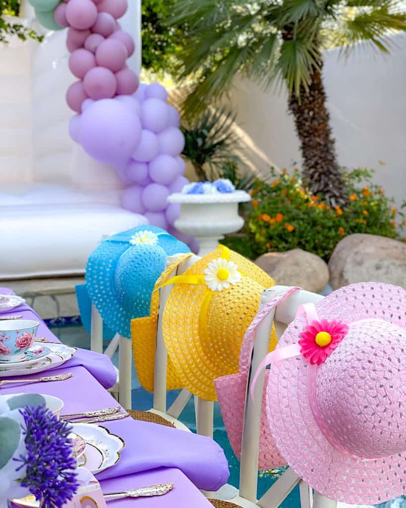Blue, yellow and pink straw hats at a birthday table