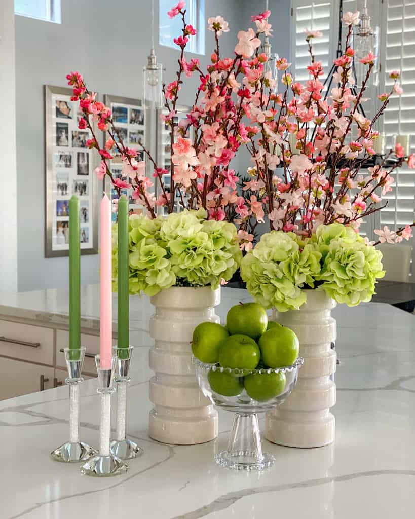 spring flowers, fruit bowl with apples and green and pink candles on kitchen counter.