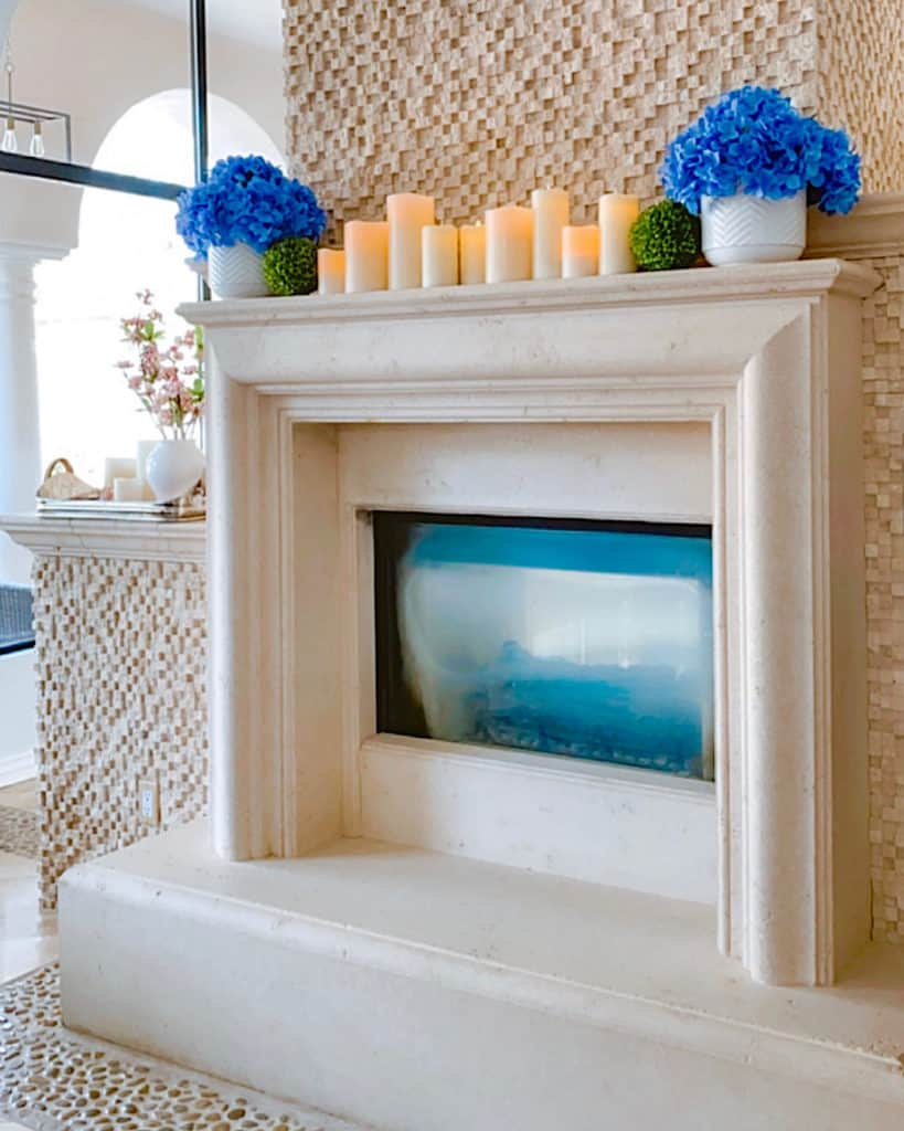 White mantel decorated for spring with candles and flowers