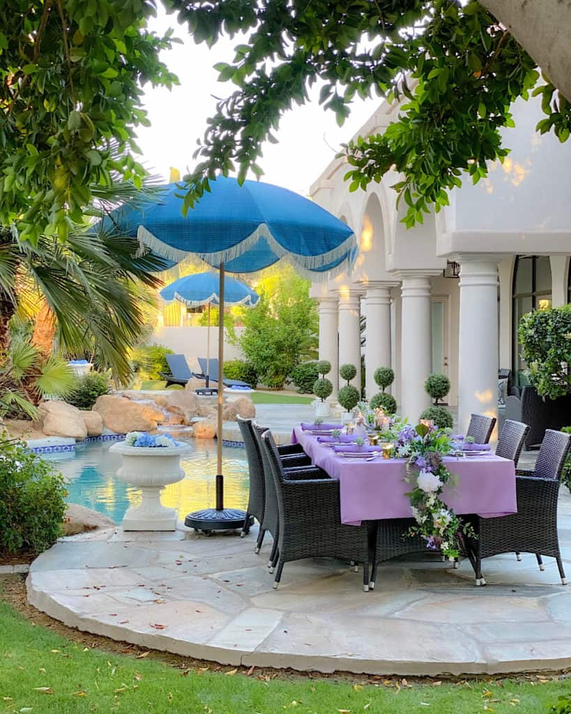 Purple and green decorated outdoor table by a pool.