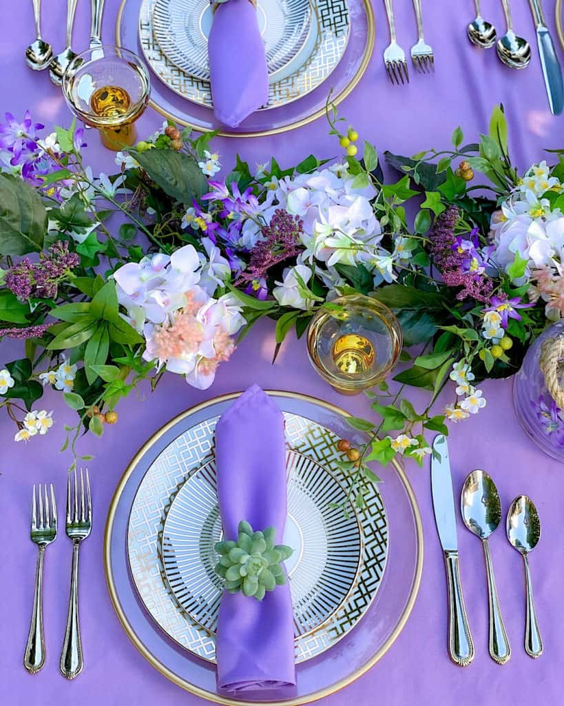 Purple napkin on flatware on purple tablecloth. Place setting for a spring outdoor brunch.