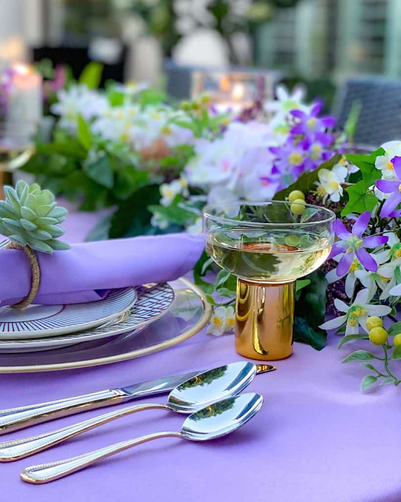 Cutlery, glass and place setting on a purple tablecloth.