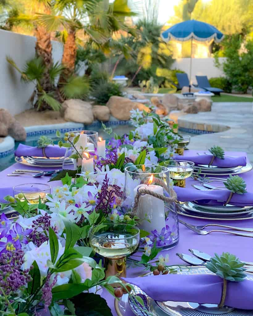 Flowers and candles and purple and green place settings on outdoor table.