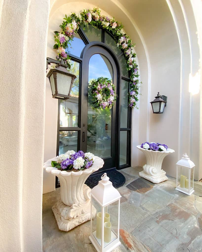 Floral displays and storm candles in a front door entranceway