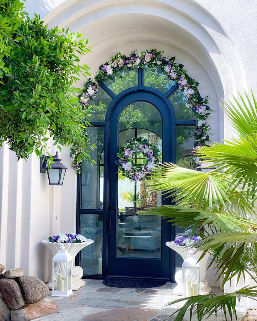 Purple and white floral arrangements in a white courtyard